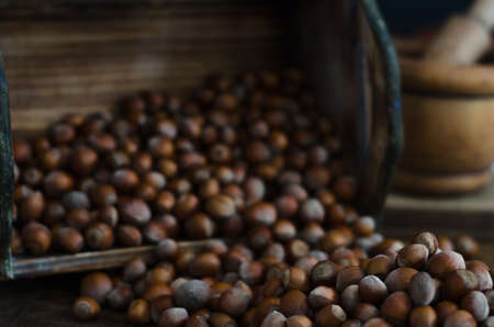 tumbling: Hazelnuts caught in motion tumbling into rustic wooden box Stock Photo