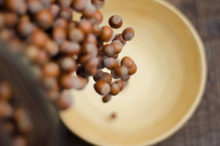 Hazelnuts caught in motion tumbling into Bamboo bowl Stock Photo