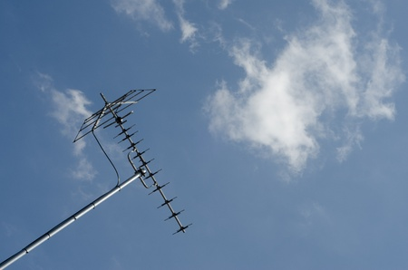 TV Antenna isolated on blue sky with luffy white clouds in the background.
