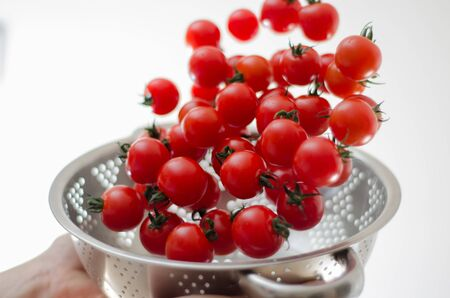 Ripe cherry tomatoes being tumbled and poured down into a silver metal colander with white background. Stock Photo