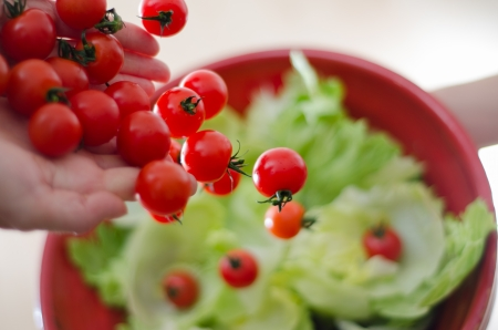 Some cherry tomatoes being poured onto lettuce.