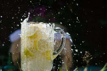 Water pouring and splahing into glass jug filled with lemons on sunny day