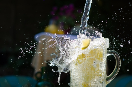 Water pouring and splahing into glass jug filled with lemons on sunny day  photo