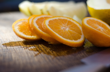Slices of freshly cut orange on an oak board with out of focus melon in background