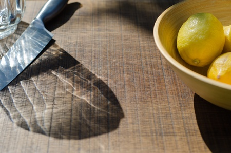 A bowl of lemons next to a knife and jug on an Oak board ready to make into lemonade on a summers day  photo
