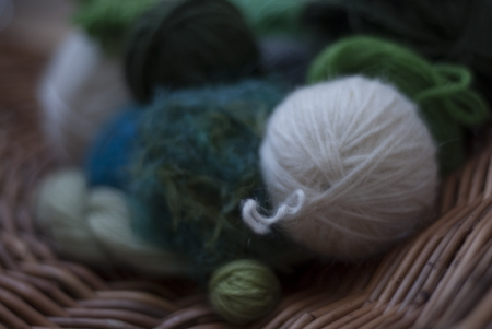 basket embroidery: Balls of wool in shades of green, blue and white and on circular willow basket weave Stock Photo