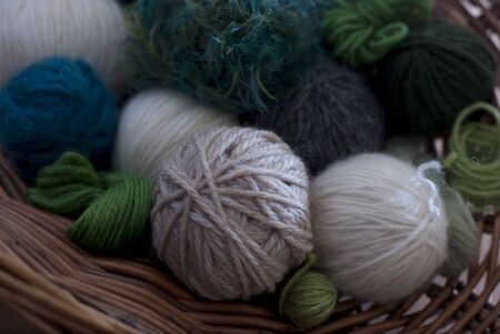 Balls of wool in shades of green, white and beige in a willow basket