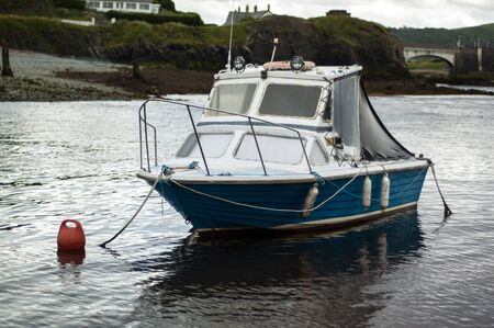 Small blue moored fishing boat with single cabin Stock Photo