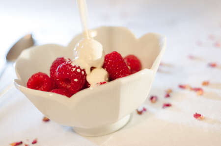 Raspberries in a white bowl with fresh cream being poured over them from a jug in a bright table top setting
