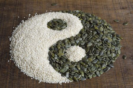 dualistic: The yin yang created out of pumpkin seeds and sesame seeds on a dark wood surface