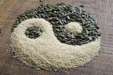newage: The yin yang created out of pumpkin seeds and sesame seeds on a dark wood surface