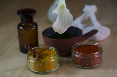 An arrangement of turmeric and cayenne spices, oil bowl and bottle, and massage poultice boluses used in Ayurveda massage, with an exotic flower  photo
