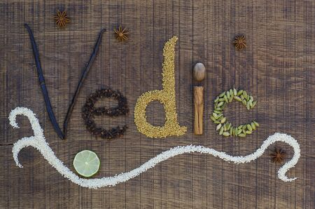 vedic: The word Vedic spelled out in a decorative way, with spices and seeds used in the ayurveda diet and healing, on a wooden countertop, surface.