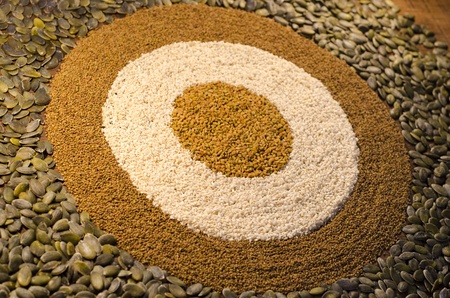 sripes: A circular, geometric pattern made from a variety of seeds, including pumpkin seeds, alfaf seeds, sesame seeds amd fenugreek seeds.