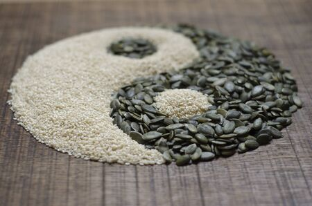The yin yang created out of pumpkin seeds and sesame seeds on a dark wood surface