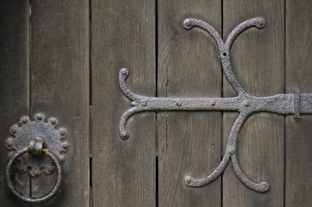 Closeup of wrought iron metal work on old oak door of church.