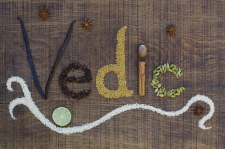 The word Vedic spelled out in a decorative way, with spices and seeds used in the ayurveda diet and healing, on a wooden countertop, surface.