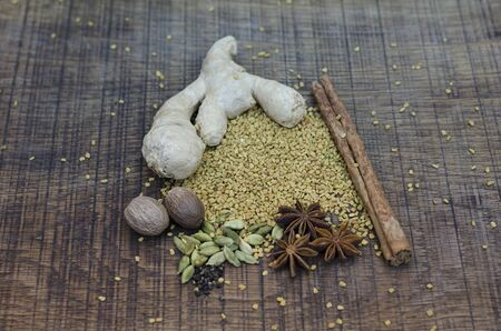 A selection of spices used in an ayurveda diet and healing, with root ginger, a cinnamon stick, cardamon pods and seeds, nutmegs and fenugreek seeds scattered on an oak wood surface. photo