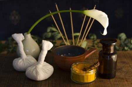 Un accordo di curcuma, spezia, ciotola l'olio e la bottiglia, e boli impacchi massaggio utilizzati nel massaggio Ayurveda, con un fiore esotico e bruciare l'incenso in background. Archivio Fotografico