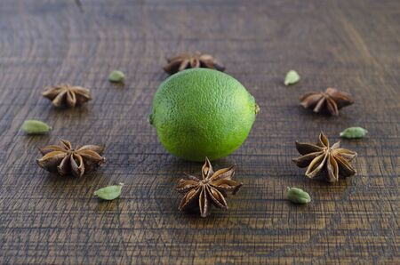 A geometric flower pattern of star anise and cardamom pods around a lime, on a dark wood surface. photo