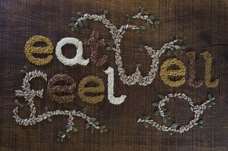 The phrase Eat Well, Be Well, decoratively written in sesame seeds, sunflower seeds, flax seeds, alfafa seeds, fenugreek seeds and pumpkin seeds, on a dark wooden surface. Stock Photo