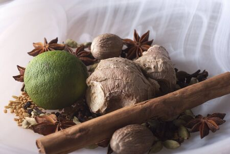 eastern health treatment: closeup of Ayurvedic ingredients, a lime with whole spices in smoky white glass bowl Stock Photo