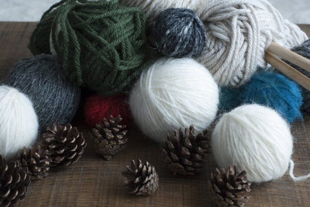Balls of lambswool in avariety of colors with wooden knitting needles and fircones.