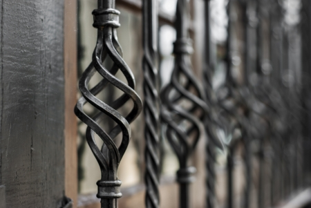 greys: A row of decorative bronze coloured metal window bars with a twisted three dimensional spiraling design fading at a diagonal perspective on the outside of the building