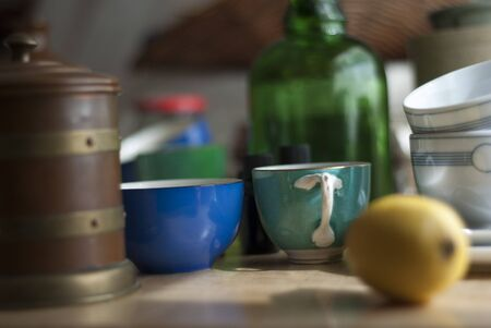a still life of odd bits and pieces of clutter, including cups, crockery and glass