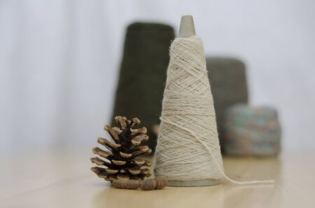 Wool Yarn spools in earthy colours with fircone photo