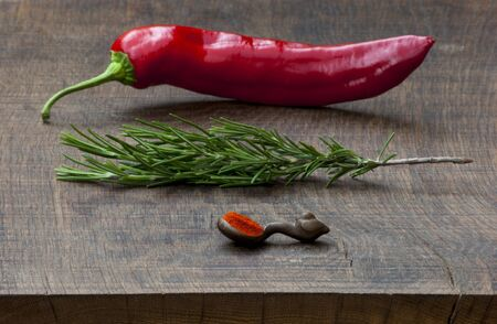 Fresh red pepper, sprig of rosemary, wooden measuring spoon of ground red pepper spice on dark, wooden chopping board Stock Photo