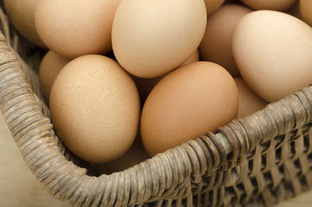 Eggs sitting in a vintage wicker basket Stock Photo