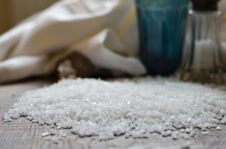 Seasalt spread on a dark wooden chopping board with soft focus napkin blue glass and salt shaker in background
