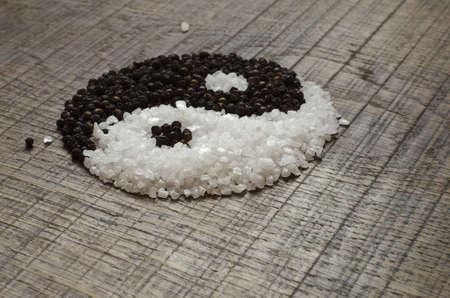 peppercorns: Seasalt and Peppercorns shaped to form a Yin Yang on an Oak Wood Chopping Board