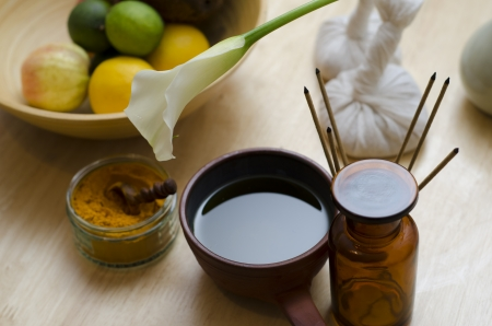 A countertop arrangement of ayurvedic turmeric spice, oil and massaging tools and an exotic flower used in Ayurveda massage
