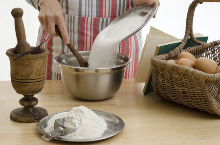 Woman baking a cake, adding the sugar to a bowl & surrounded by the other ingredients. Stock Photo