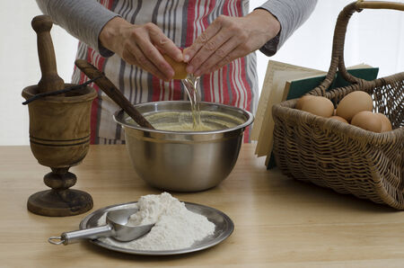 Woman baking a cake, adding an egg to a bowl, surrounded by the other ingredients