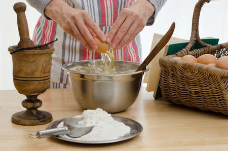 Hands adding egg to a bowl, surrounded by the other ingredients and a recipe book  Stock Photo