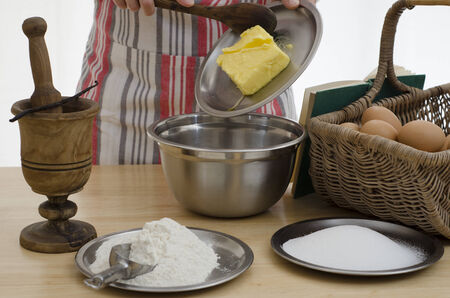 Person baking a cake, adding the butter to a bowl   surrounded by the other ingredients Stock Photo