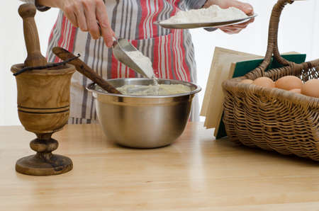 Woman baking a cake, adding flour to a bowl, surrounded by the other ingredients and a recipe book Stock Photo
