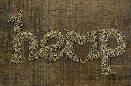 The word Hemp written artistically in hemp seeds on a wooden chopping board, with a heart shape integrated into the word  Stock Photo
