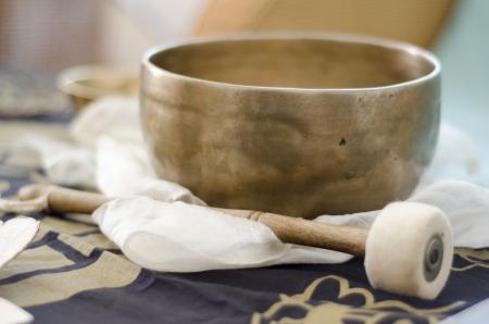 singing bowl: Una bella mano battuto, ciotola tibetana di canto con il bastone plaed su una sciarpa bianca buddhisti