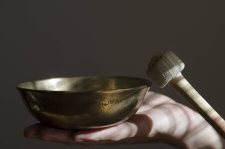 A Tibetan singing bowl sitting in a hand being played with a baton  Stock Photo - 24976930
