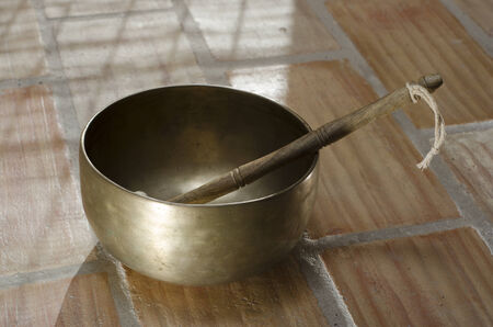 enhanced health: A Tibetan singing bowl sitting on a tiled floor with a baton resting inside  Stock Photo
