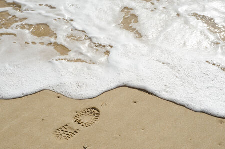 Boot Footprints left behind behind from somone waking along the shore Stock Photo