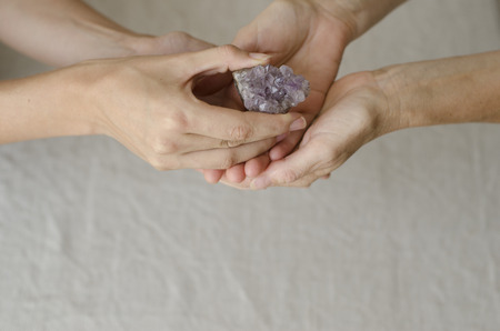 enhanced health: Womans hands holding and placing an amethyst crystal in another womans hands in healing gesture.