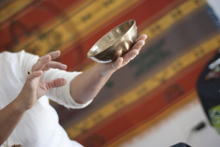 A Tibetan singing bowl in the hands of a therapist