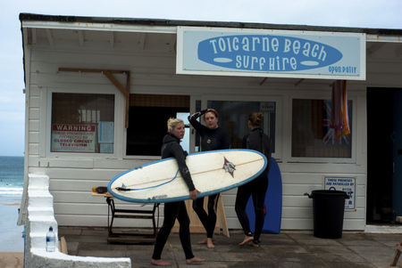 Female surfers in wetsuits with surf board outside a surf hire kiosk  at Toicarne Beach in Cornwall