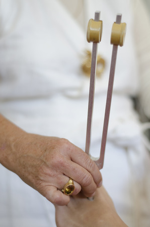 complementary therapy: Close up of practitioner giving healing tuning fork treatment.