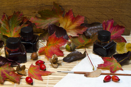 Arrangement of autumn leaves, nuts and berries,  bottles of coloured ink, around paper and paintbrus with wooden oak background and room for text.